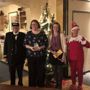 The Conductor and Gladys, the Head of Elf on the Shelf's , pose with the winners at a Holiday show.
